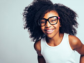 Happy little African girl with long curly hair wearing glasses while standing by herself against a gray background