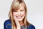Laughing young blond woman with eyes closed