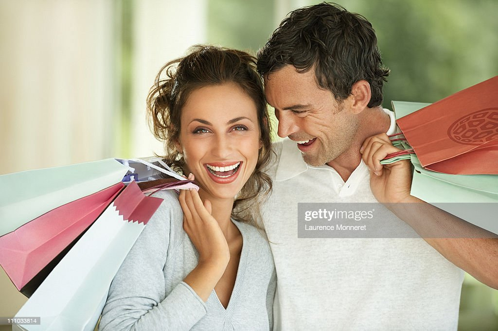 Laughing young couple with shopping bags