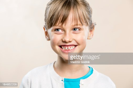A laughing young girl looking away : Stock Photo