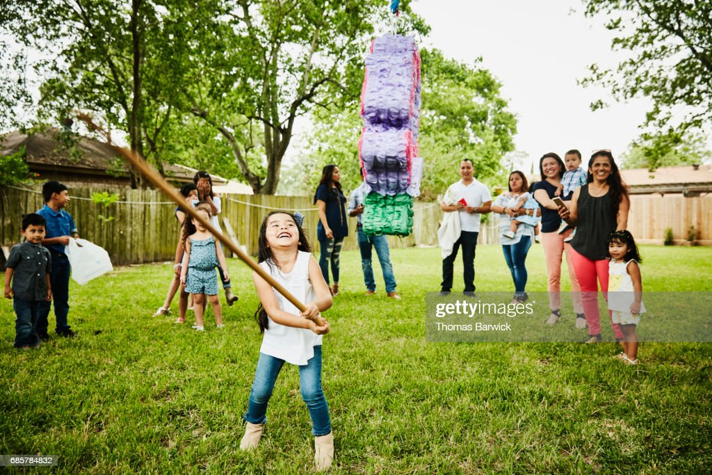 Laughing young girl trying to break open pinata during family birthday party in backyard : Stock Photo