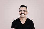 Young male with glasses and mustache, grey background, studio shot, laughing