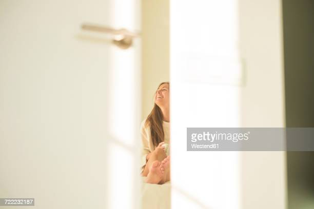 Laughing young woman behind bedroom door sitting on bed with cup of coffee