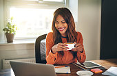 Laughing young African female entrepreneur drinking a cup of coffee and working on a laptop while sitting at a desk in her home office