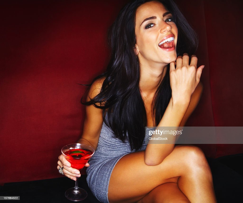 Laughing young woman holding a glass of martini