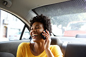 Closeup portrait of laughing young african woman sitting on a back seat of a car and talking on mobile phone