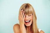 Joyful young woman laughing in studio