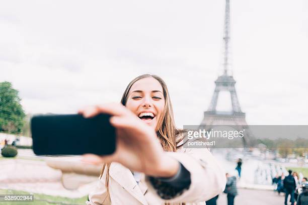 Laughing young woman making selfie at Eiffel tower