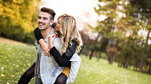 Laughing young woman piggyback riding her boyfriend