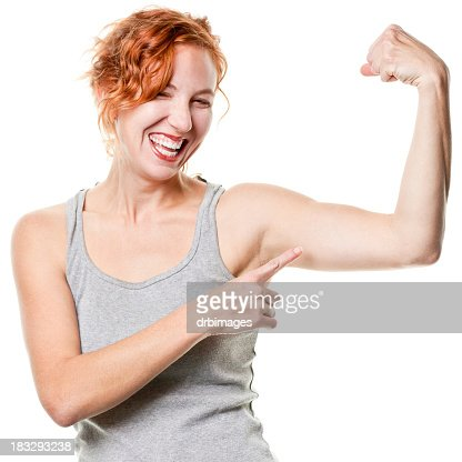 Laughing Young Woman Shows Arm Muscle