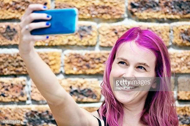 Rire Jeune femme prenant selfie sur son magenta-Cheveux teints en rose
