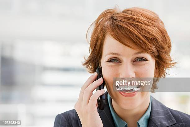 Laughing young woman using cellphone