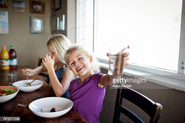 Lauging girl rasing glass of water towards camera