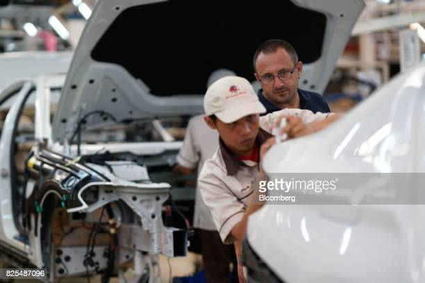 A BMW launch trainer oversees an employee assembling a BMW 530i sedan on the production line at a PT Gaya Motor plant in Jakarta Indonesia on...