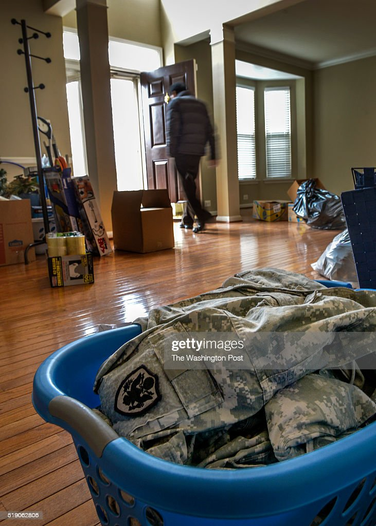 A laundry basket foreground filled with military garments as the house owner walks through in the house where Ronnie Hamilton shot and killed his...