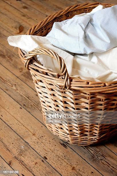 Cesta de la ropa sucia en piso de madera