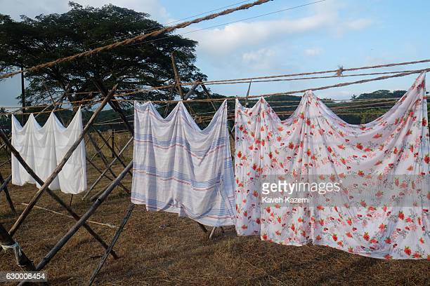 Laundry clothing washed in a stone bath hangs on the line at an openair laundry facility