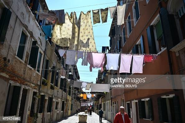 Laundry dries hanged between buildings in a street of Venice on May 7 2015 AFP PHOTO / GABRIEL BOUYS
