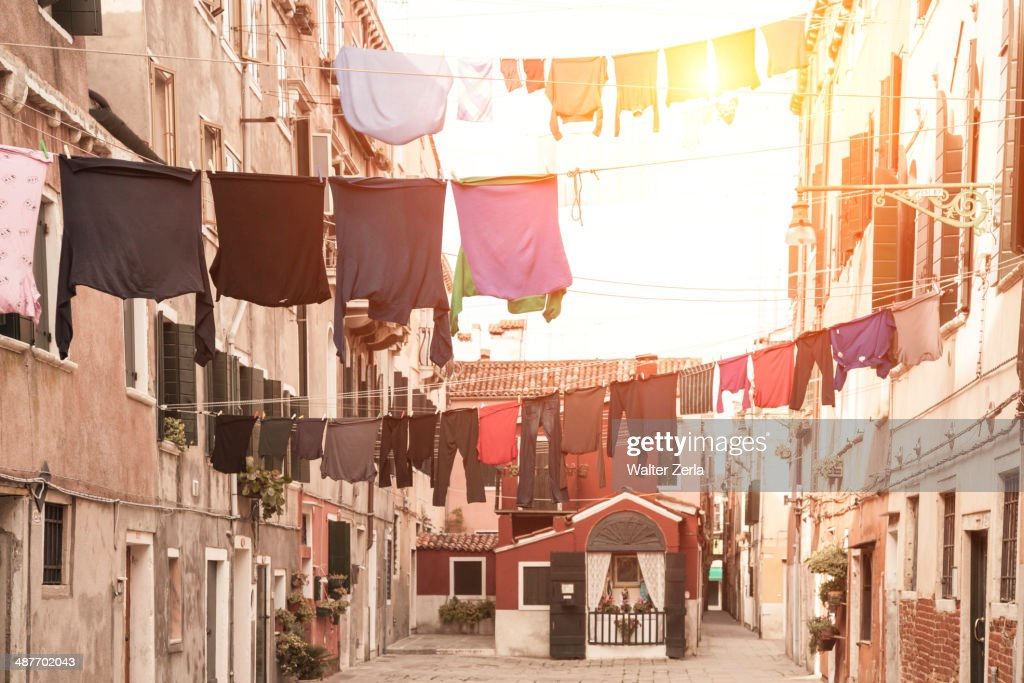 Laundry hanging from apartment buildings : Stock Photo