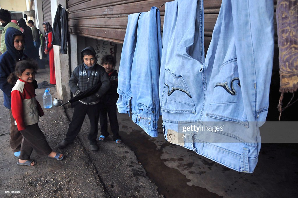 Laundry hangs outside a partially shuttered room as Syrian refugee children stand outside in Kfarkahel village, in the Koura district close to the northern city of Tripoli on January 9, 2013, as stormy weather sparked widespread flooding, prompting chaos on the roads and a nationwide school closure. The number of Syrian refugees in Lebanon is already totaling 156,000, according to UN figures, and 200,000 according to the Lebanese government estimates.
