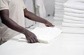 Hands of an african male laundry hotel worker folds a clean white towel. Hotel staff workers. Hotel linen cleaning services.