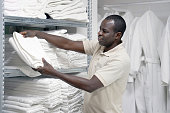 Hotel worker African man lays a clean white towel on the shelves. Hotel staff workers. Hotel linen cleaning services.