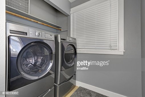 Laundry interior with gray walls, carpet and modern appliances. : Stock Photo