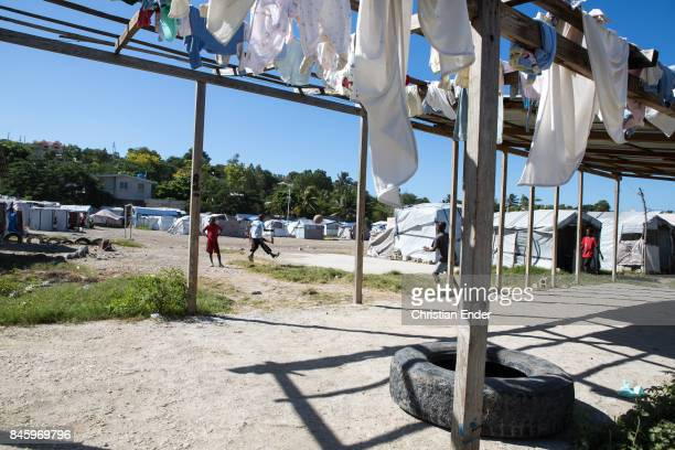 PortauPrince Haiti December 09 2012 Laundry is hanging in the sun to dry while children playing soccer in the background the refugee camp Parc Colofe...
