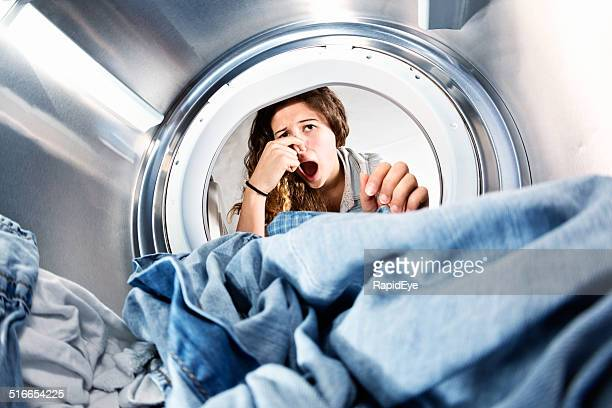 Laundry left in clothes dryer stinks! Unhappy woman holds nose.