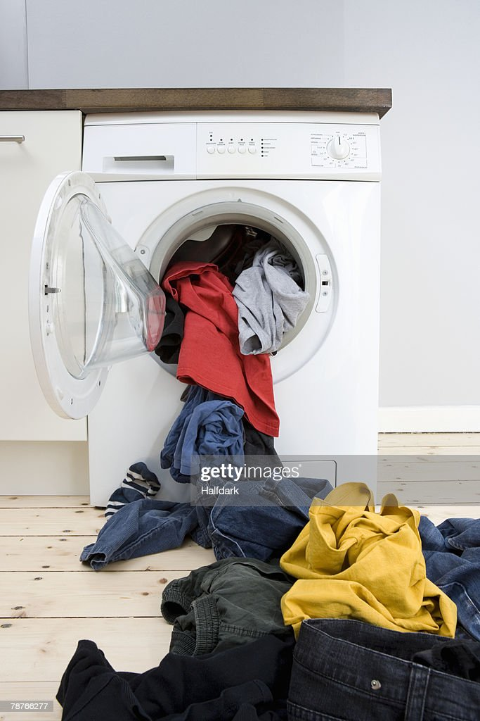 Laundry spilling out of a washer dryer