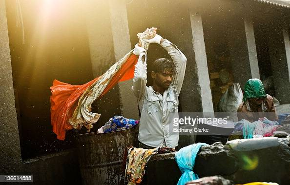 Laundry workers flogs clothes at Dhobi Ghat on November 4 2011 in Mumbai India Dhobi Ghat is known as the world's largest laundry with 800 wash pens...