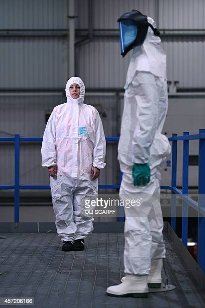 Laura Anderson an employee at Arco safety equipment supplier poses for pictures as she wears a protective suit at the company's warehouse in Hull...