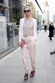 Laura Bailey wearing Christopher Kane top Balenciaga Cardigan Sessun trousers Miu Miu shoes and Radley clutch street style at London fashion week...