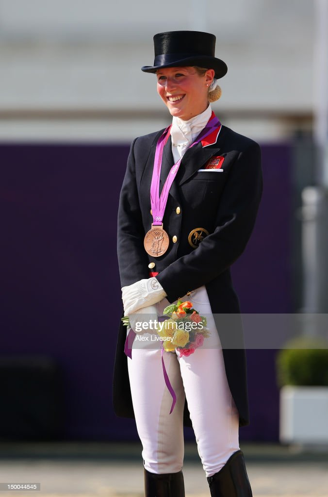 Laura Bechtolsheimer of Great Britain riding Mistral Hojris celebrates with her bronze medal during the medal ceremony following the Individual...