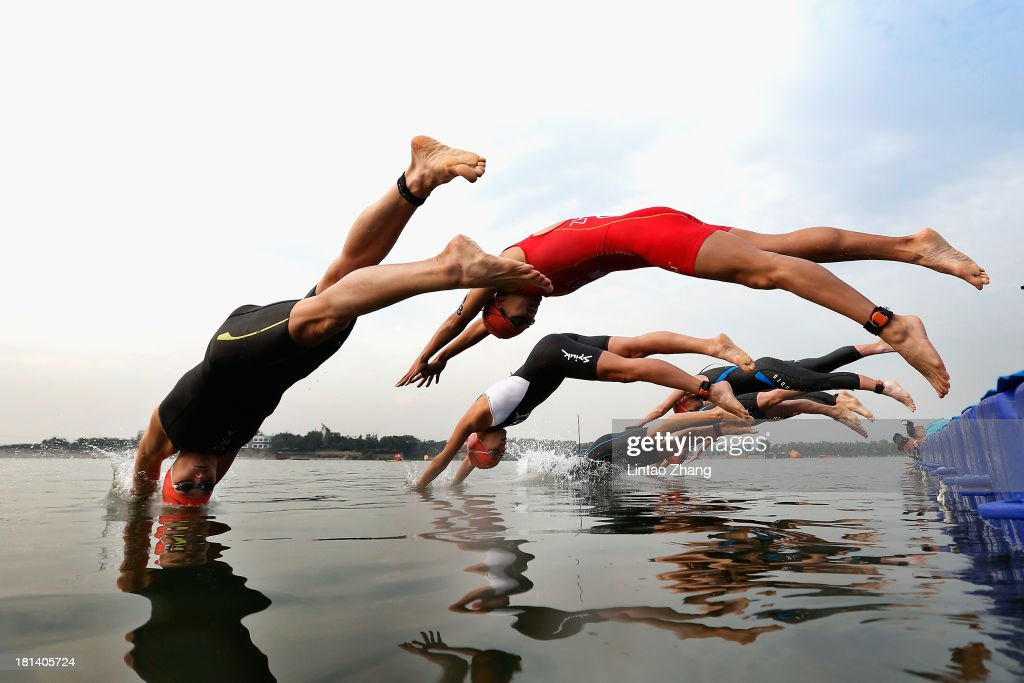 Laura Bennett (L) of the United States jumps into the water during the swimming stage of the 2013 Beijing International Triathlon at Qinglong lake park Fengtai District on September 21, 2013 in Beijing, China.