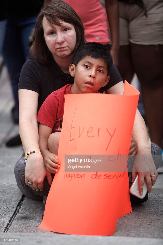 Laura Boudon and her 7 year old son Lucas listen to speakers as demonstrators hold a peaceful rally at the Torch of Freedom in downtown Miami a day after the verdict to the George Zimmerman murder trail on July 14, 2013 in Miami, Florida. A jury found neighborhood watch volunteer, George Zimmerman not guilty of shooting and killing 17-year-old Trayvon Martin after an altercation in February 2012.