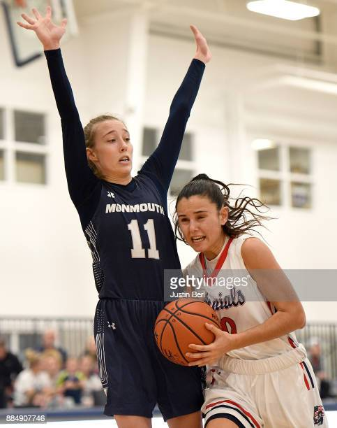 Laura Carrasco of the Robert Morris Colonials drives to the basket against Kayla Shaw of the Monmouth Hawks in the second half during the game at...