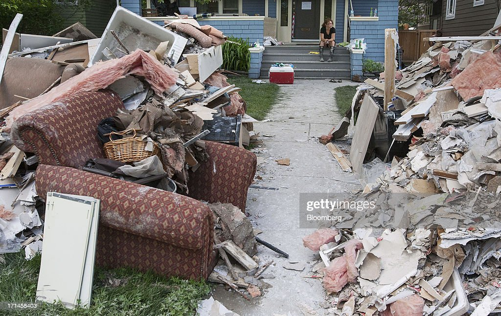 Laura Colpitts sits on the front porch of her Elbow Park home as debris and damaged belongings sit in piles after flooding in Calgary, Alberta, Canada, on Monday, June 24, 2013. Water levels in Calgary subsided and crews are working to restore power as officials confirmed a fourth fatality in the worst flood in Alberta's history. Photographer: Keith Morison/Bloomberg via Getty Images