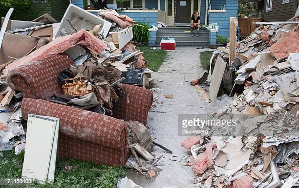 Laura Colpitts sits on the front porch of her Elbow Park home as debris and damaged belongings sit in piles after flooding in Calgary Alberta Canada...