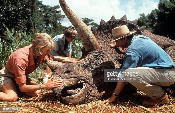 Laura Dern and Sam Neill come to the aid of a triceratops in a scene from the film 'Jurassic Park' 1993