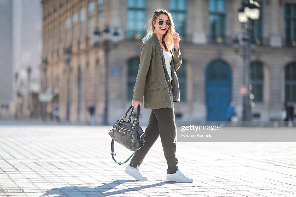 Laura Girard (fashion blogger - The Stilletoholic), is wearing a Zara green jacket, Zara green pants, an H&M white top, Adidas shoes, a Balenciaga black bag, and Ray Ban sunglasses, during a street style session, at Place Vendome, on May 06, 2016 in Paris, .