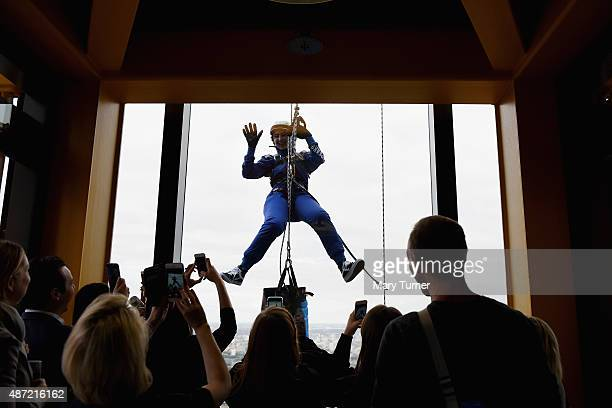 Laura Kwong from 'Team Laithwate' waves to her friends watching on the viewing platform at Floor 42 as she abseils down the skyscraper known as the...