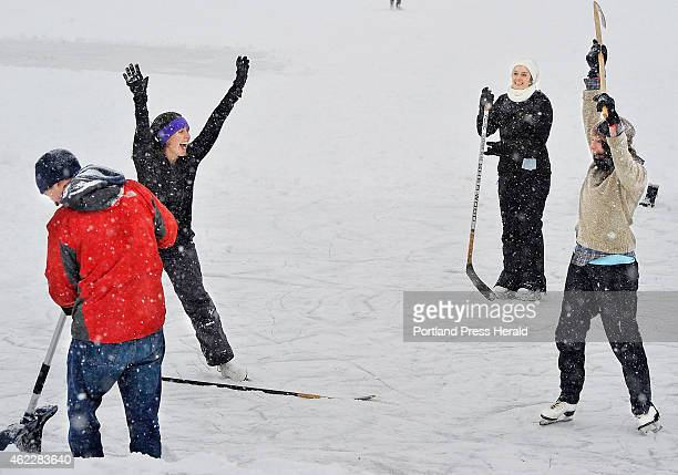 Laura Mailander left celebrates the women's team's first goal ever with teammate Laura Fralich right and Caroline Jova back as they play pond hockey...