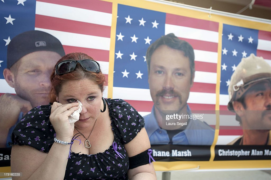 Laura Marshall, 29, of Phoenix, Arizona sits in front of a photograph of her cousin, Garret Zuppiger (L) who was one of the 19 firefighters killed in a wildfire, at the entrance to a memorial service in their honor at Tim's Toyota Center July 9, 2013 in Prescott Valley, Arizona. The firefighters, of the Granite Mountain Hotshots crew, died battling the fast-moving blaze on June 30.
