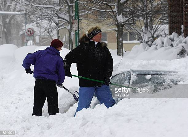 Laura Robinson and Marty Dickinson of shovel out their car from a pile of snow December 28 2001 in Buffalo NY The city of Buffalo is under a state of...