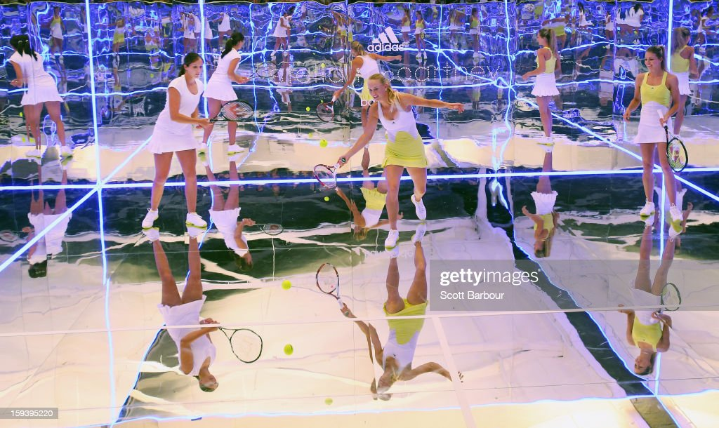 Laura Robson (L) of Great Britain and Maria Kirilenko (R) of Russia watch as Caroline Wozniacki of Denmark plays a shot on a mirror court at the Adidas by Stella McCartney media launch on January 13, 2013 in Melbourne, Australia. To globally launch the first adidas by Stella McCartney collection tennis players Caroline Wozniacki, Maria Kirilenko and Laura Robson played tennis in the world's first mirror court.