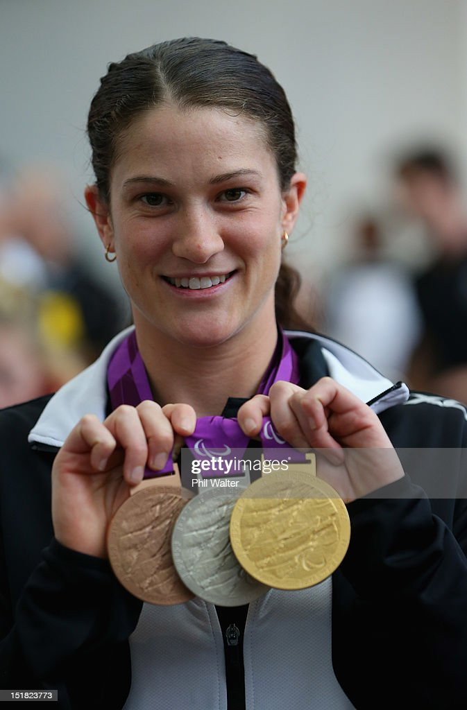Laura Thompson holds up her medals from the London Paralympics, during the New Zealand Paralympians arrival home at Auckland International Airport on September 12, 2012 in Auckland, New Zealand.