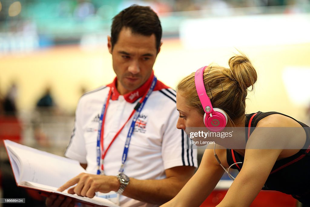 Laura Trott of Great Britain talks with coach Chris Newton (L) as she warms up on day three of the UCI Track Cycling World Cup at Manchester Velodrome on November 3, 2013 in Manchester, England.