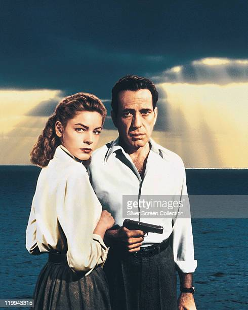 Lauren Bacall US actress and Humphrey Bogart US actor holding a handgun in a publicity portrait issued for the film 'Key Largo' with the sea in the...