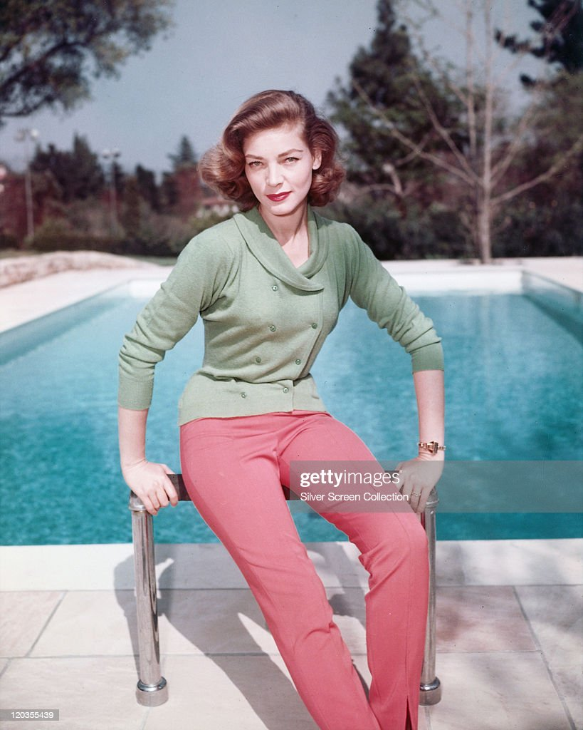 Lauren Bacall US actress weaing a green doublebreasted cardigan and red trousers as he poses beside a swimming pool circa 1950